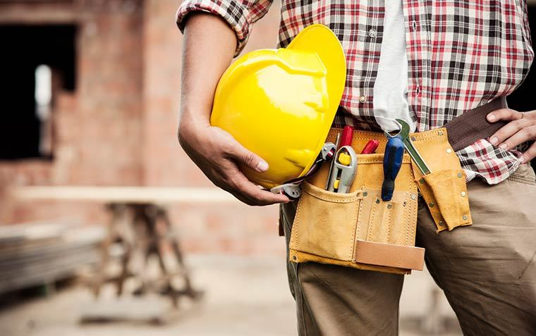 Tradie holding their hardhat on their hip with their tool-belt