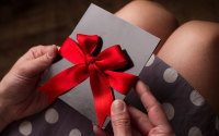 Woman opening a gift voucher in a red bow